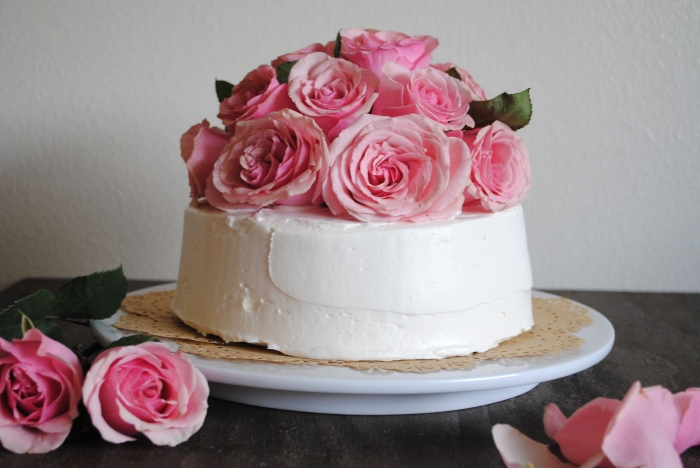 Cake covered with swiss meringue buttercream and fresh cut roses