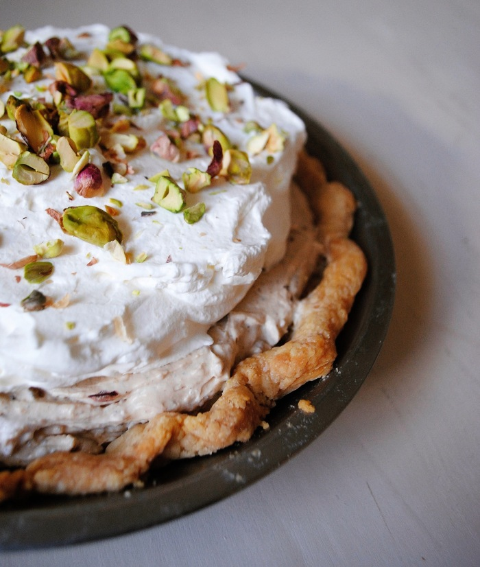 Buttery pie crust lined with chocolate ganache, filled with earl grey pastry cream, whipped cream, and topped with pistachios