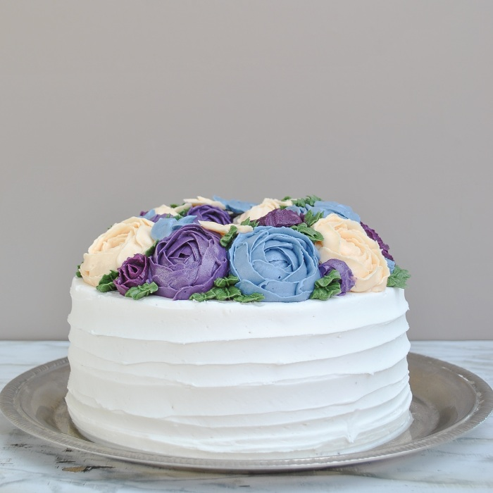 Cake is covered with swiss meringue buttercream and buttercream roses